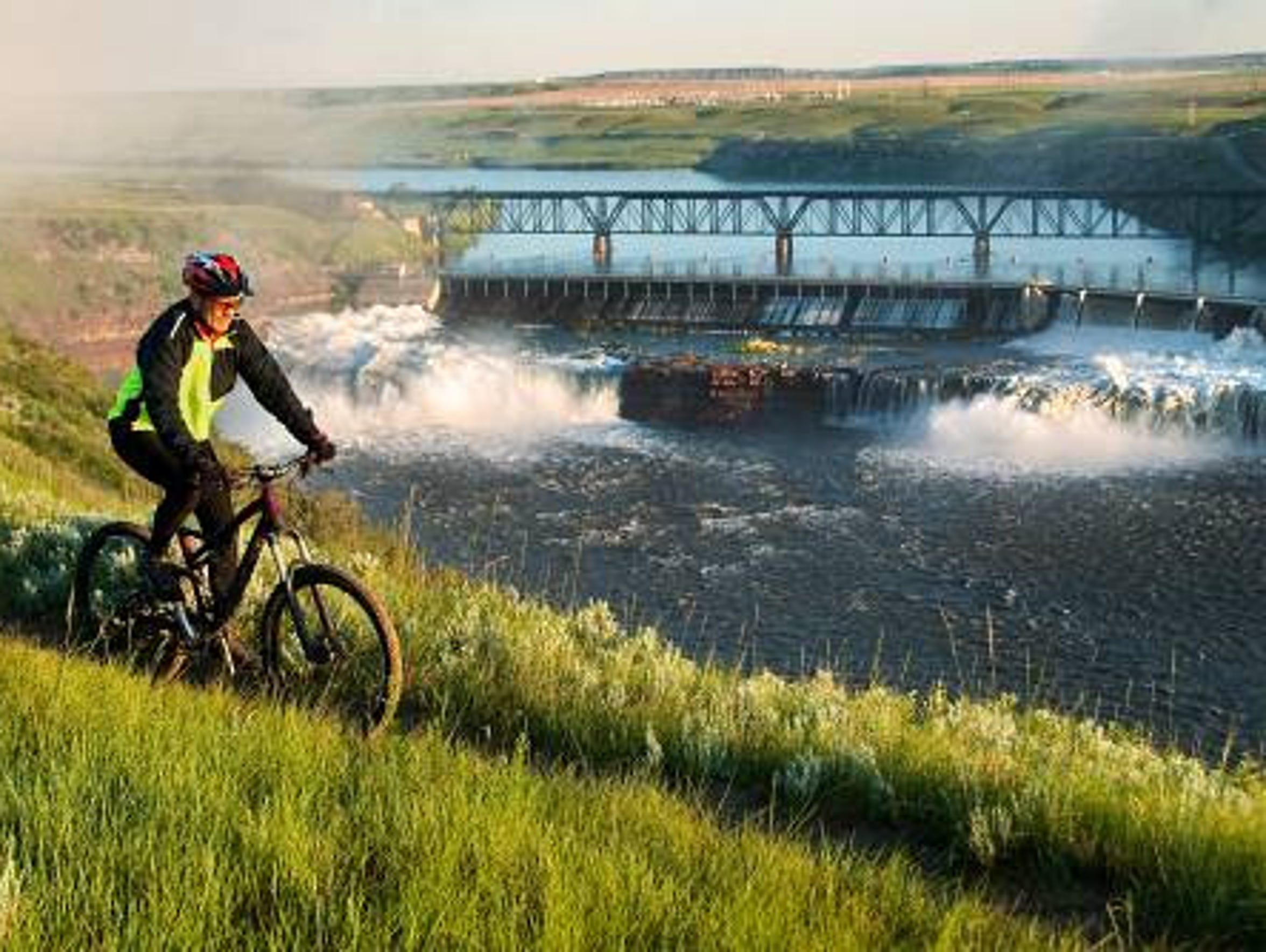 A bicyclist rides along the River's Edge Trail above