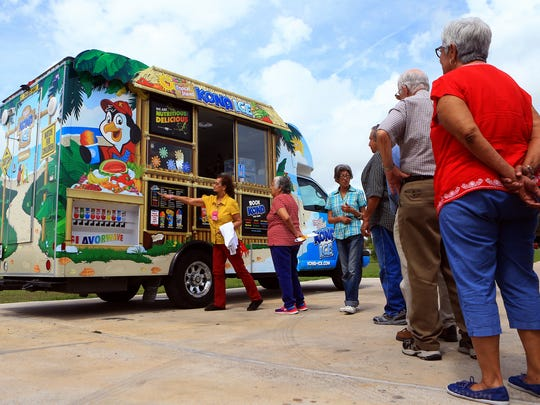 Community members from Lindale Senior Center stand in line to receive a free snow cone as Reliant Energy opens its annual Beat the Heat Center on Wednesday, May 31, 2017, in Corpus Christi.