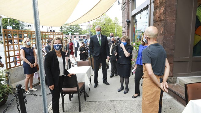 Gov. Charlie Baker held his Thursday COVID-19 news conference at Bistro 5 in Medford, where Jersey barriers enclose a curbside dining area.