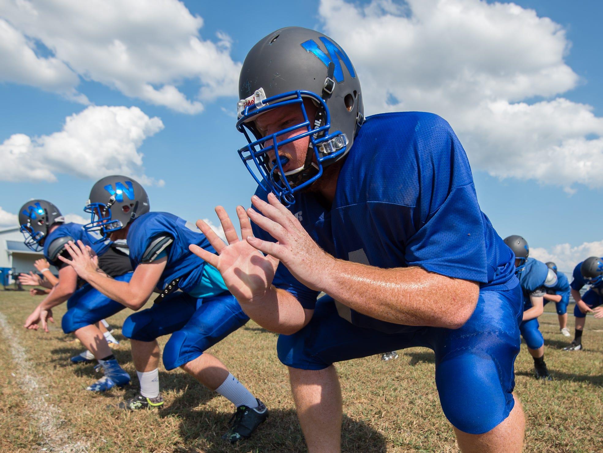 Woodbridge High School football linemen Brian Ireland runs linemen drills at practice.