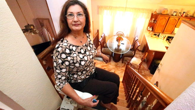 Martha R. Torres gets upstairs in her Eastside tri-level home with the aid of two lift chairs provided in part by the Seniors Fund. Torres, 62, considered selling the home until the lifts were installed.
