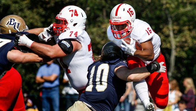 St. John's University running back Antoine Taylor tries to leap over  Bethel University linebacker Josh Dalki but is brought down during the first half Saturday, Oct. 1, in Arden Hills.