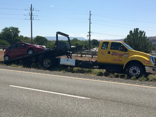 A red Nissan Versa that was involved in a secondary accident after a Mustang was driven into a guardrail during what witnesses described as a road rage incident is loaded onto a flatbed tow truck in the median of Interstate 15 Thursday near mile marker 11.