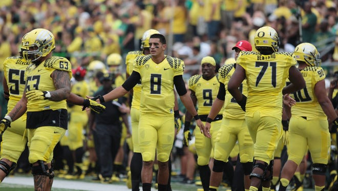 Oregon Ducks quarterback Marcus Mariota (8) celebrating with the special team against the Tennessee Volunteers.