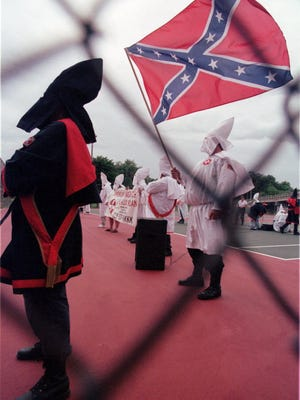 Unidentified members of the Ku Klux Klan gather and wave a Confederate flag in Three Rivers, Mich., in this July 17, 1999, file photo.