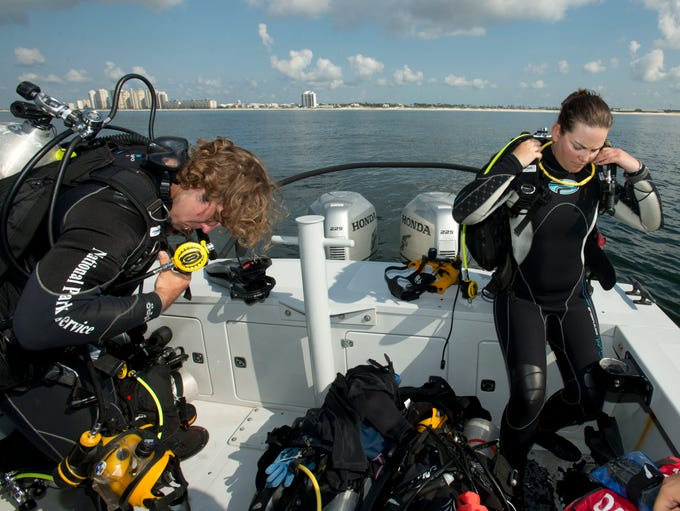 National Parks Service Submerged Resources Divers John Bright, left, and Jessica Keller, right, prepare for a dive off Perdido Key Thursday afternoon. The NPS team has been working on the Gulf Coast doing a survey in park waters since April.