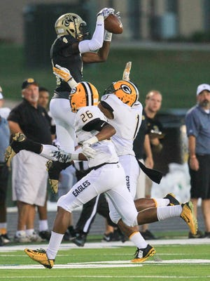T.L. Hanna's Aj Bryant leaps for a catch near Greenwood's Will Culbreath during the first quarter at T.L. Hanna High School in Anderson.