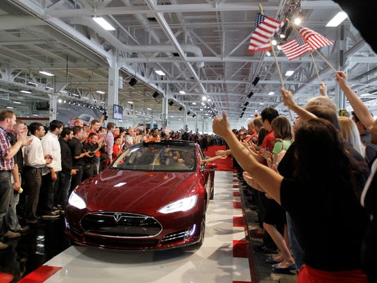 Tesla workers cheer on the first Tesla Model S cars sold during a rally at the Tesla factory in Fremont, Calif., on June 22, 2012.  The factory has been accused of allowing worker discrimination and harassment to go unchecked.