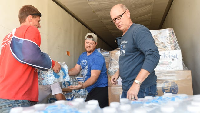Jason Knuckles (left), of Care Center Ministries, Patrick Grissom of Christ Community Church, (middle) and David Johnson, senior pastor for Christ Community Church, load a semi-tractor trailer Thursday morning. The items will be distributed to people who have been affected by Hurricane Harvey.