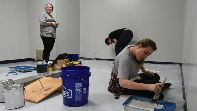 Mountain Home Youth Alliance members (from left) Nikki Golden, 15, of Flippin, Ace Harden, 15, of Calico Rock and 16-year-old Layla Rasico of Flippin paint the teacher's lounge at Mountain Home Junior High School on Tuesday.