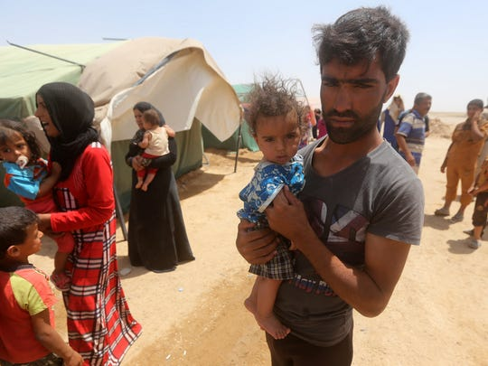 Iraqis who fled Ramadi after it was seized by Islamic State militants gather during a sandstorm at their camp south of Fallujah on May 22.