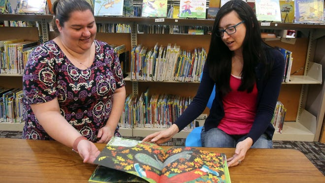 From left, Childrens Programmer Brittany Jones and Tech Services Librarian Meghan Blackburn discuss what books to use for three Cleveland County Library System StoryWalks in the future.