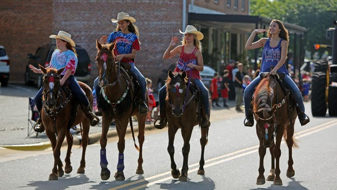 Riders wave from atop their horses at the Lattimore Fourth of July parade.