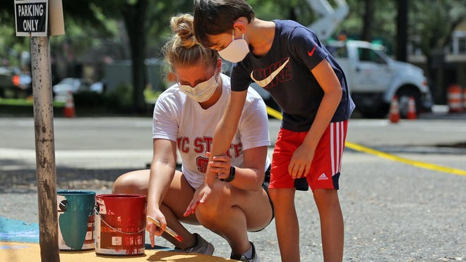 Felicity Hoppes helps Andrew Hayes, 7, make his mark on a mural in uptown Shelby on Thursday.