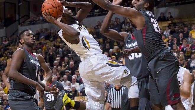 Missouri's Tramaine Isabell, center, tries to shoot over Arkansas' Manuale Watkins, right, and in front of Trey Thompson, left, during the first half Tuesday night in Columbia.