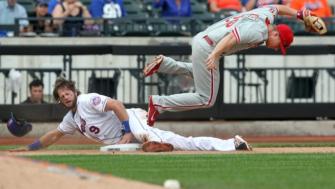New York Mets right fielder Kirk Nieuwenhuis steals third base ahead of a tag by Phillies third baseman Cody Asche during the eighth inning Sunday at Citi Field in New York.