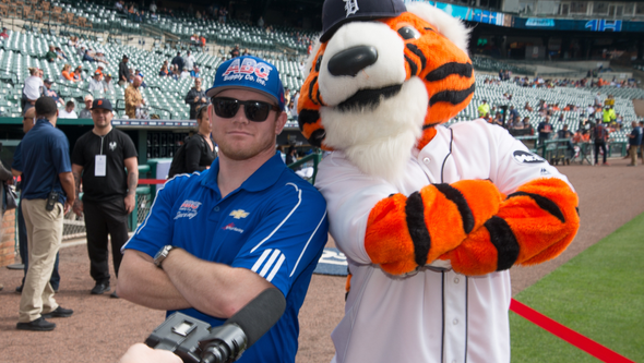 Conor Daly posing with Paws before throwing out the