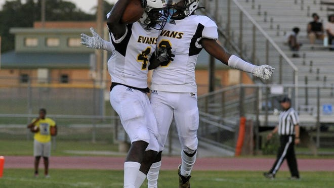 Two Evans football players celebrate after a touchdown during Friday night's season opener between Evans and Cross Creek. Evans won 58-0.
