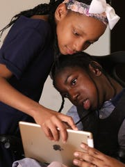 Sister Tailiyah Rush holds a computer tablet for Tochmirra Rush who is working on motor skills to interact with the device.
