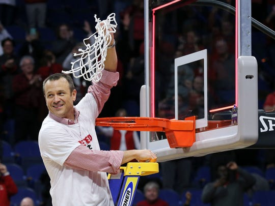 Louisville head coach Jeff Walz cuts down the net after