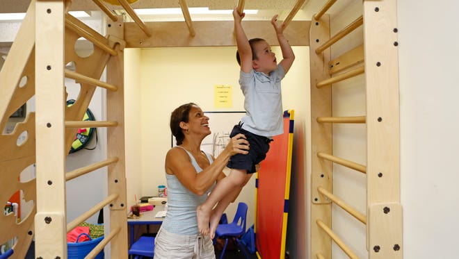 Harrison Mueller, 3, works with occupational therapist Yvonne Melendez-Cruz on Aug. 1 at Westchester Therapy Solutions in White Plains. Mueller is receiving the therapy to improve his overall function, including motor planning, motor coordination and sensory regulation.