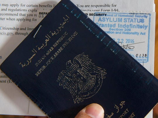 Michal Chabo holds his Syrian passport and letter granting
