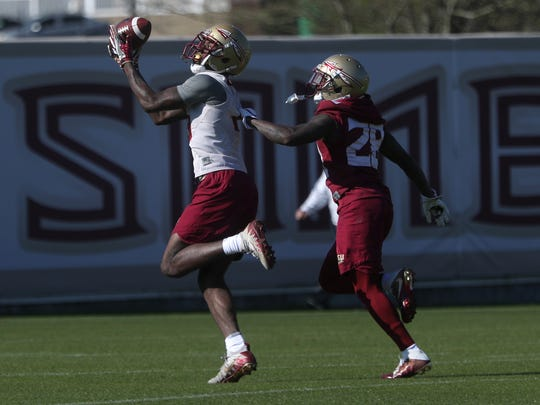 FSU's Tamorrion Terry catches a pass over Levonta Taylor during spring practice at the Al Dunlap Training Facility on Wednesday, March 21, 2018.