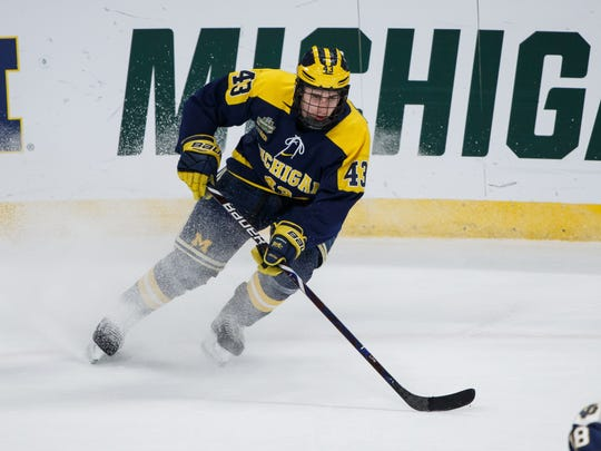 Michigan Wolverines defenseman Quinn Hughes (43) skates with the puck in the third period against Notre Dame Fighting Irish in the 2018 Frozen Four college hockey national semifinals at Xcel Energy Center.