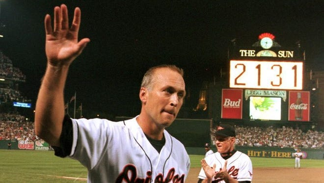 Cal Ripken Jr. waves to the crowd as the sign in centerfield reads 2,131, signifying Ripken had broken Lou Gehrig's record of playing in 2,130 consecutive games.