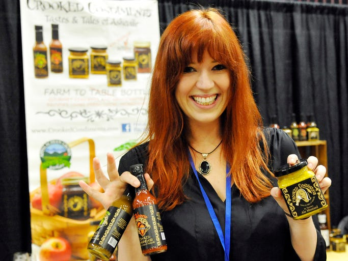 Chelsea Madison, of Crooked Condiments, shows off locally-made mustard and hot sauces. More than 100 local and international wineries, breweries, distillers, restaurants, farmers and artisan food producers participated in the Grand Tasting as part of the Asheville Wine and Food Festival at the U.S. Cellular Center Saturday. 8/23/14. Robert Bradley (rbradley@citizen-times.com)