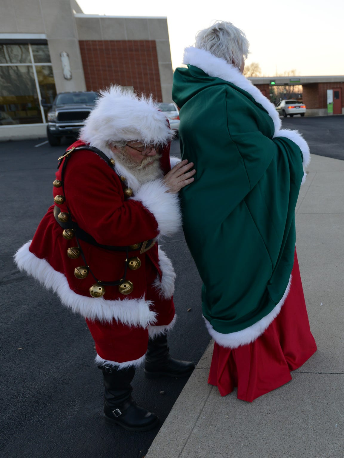 Tim Etienne hides behind his wife Ginny Etienne as he interacts with children as they wait to be picked up before the Canal Winchester holiday light parade, Friday, Dec. 1, 2017. Tim often pretends to be shy when children are afraid or shy around Santa Claus.