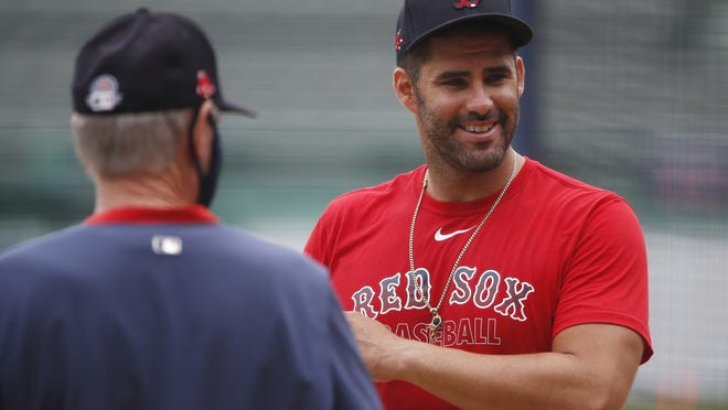 Boston Red Sox's J.D. Martinez talks with manager Ron Roenicke during baseball practice at Fenway Park, Sunday, July 5, 2020, in Boston.