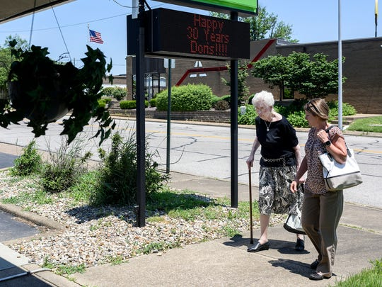 While walking back to the Lampion Center, Dorris Bedillion and her co-worker Emily Morrison, Clinical Services Director, pass a sign congratulating Bedillion on her 30-year work anniversary, Wednesday afternoon, June 6, 2018. Bedillion, Morrison and Jennifer Childress (not pictured) had lunch together at Cork 'n Cleaver before going back to the office for a party held in Bedillion's honor.