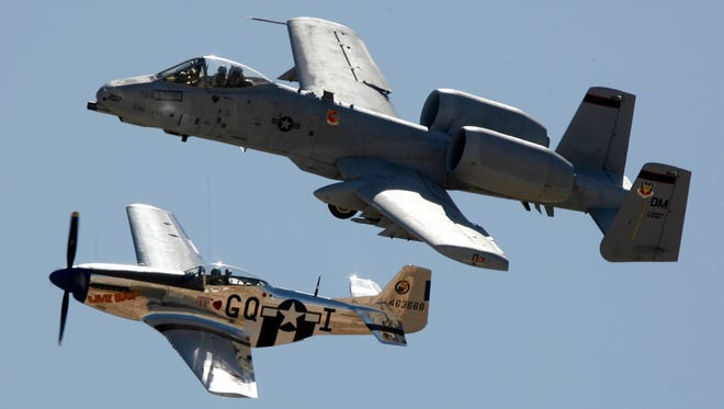 An A-10 Thunderbolt II, top, flies with a P-51 Mustang.