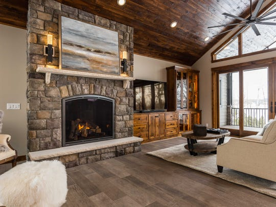 Lake views are tempered only by the stone arched fireplace that reaches up to the room's vaulted ceiling which is finished in a distressed pine