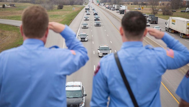 Grimes firemen salute on the 86th Street overpass over I-80/I-35 to pay respects to police officer Susan Farrell, Des Moines Police Dept. as her funeral procession passes by Wednesday March 30, 2016, after her funeral at Lutheran Church of Hope in West Des Moines.
