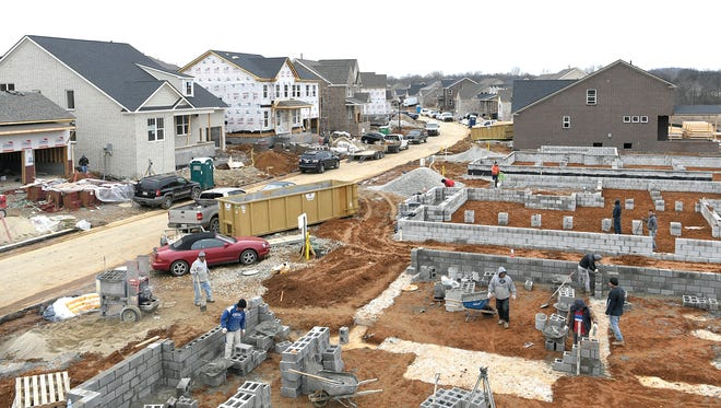 Workers build the foundation to several new homes in Enderly Pointe at Ladd Park in Franklin, Tennessee on Wednesday, Feb. 7, 2018.