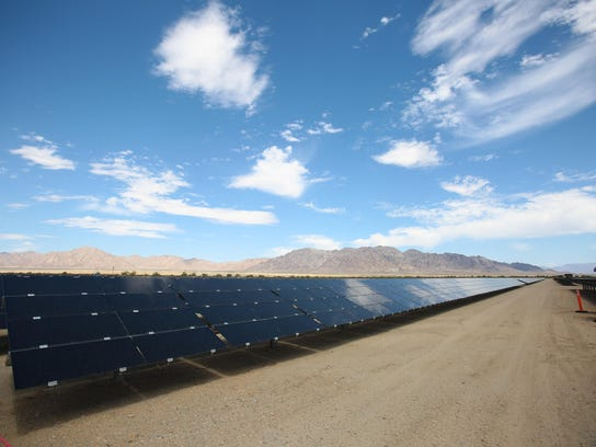 A row of solar panels reflects clouds overhead at the