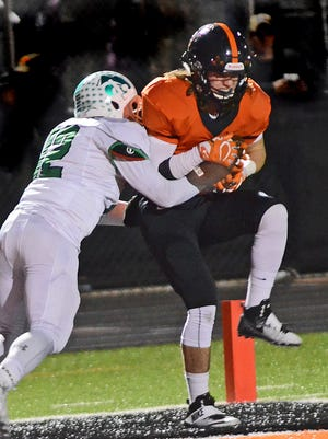 Chad Rensi catches an 11-yard pass in the end zone against Novi defender Aahmaud Jenkins for Brighton's only touchdown in a 38-9 loss.