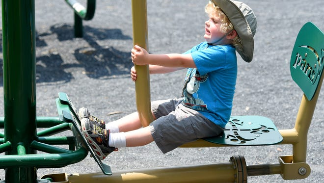 Indy Mueller, 3, of Staunton gives his all as he strains against the counterweights of the leg-press machine, but he gets it done. Indy plays briefly on the equipment at the outdoor fitness area at Gypsy Hill Park before heading up the hill to the much bigger playground on Wednesday, July 1, 2015.
