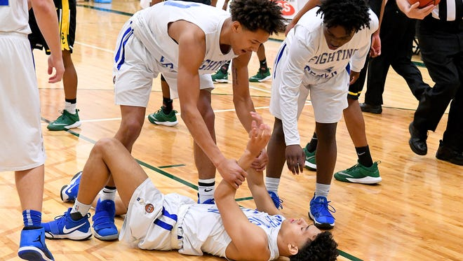 Robert E. Lee's Jarvis Vaughan and Jahleel Pettiford help teammate Jalen Henderson up after he goes down during a VHSL Class 2 boys state quarterfinal game played in Fishersville on Friday, March 2, 2018.