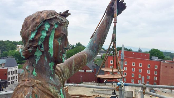 The statue of Lady Justice with her scales on top of the Augusta County courthouse.