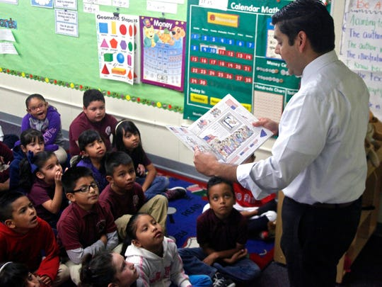 "Congressman Raul Ruiz reads Lynne Cheney's book ""America: A Patriotic Primer"" to a group of children during his visit to Mecca Elementary School on Thursday."