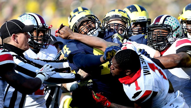 Michigan's Delano Hill is punched by Ohio State's Dontre Wilson during the second quarter on Nov. 30, 2013, at Michigan Stadium.