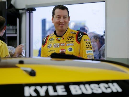 Kyle Busch smiles in the garage before practicing for the Daytona 500 NASCAR auto race at Daytona International Speedway in Daytona Beach, Fla., on Wednesday, Feb. 17, 2016. (AP Photo/Terry Renna)