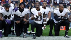 Baltimore Ravens players kneel down during the playing