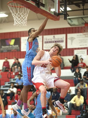 Lenape's Andrew Sims, right, leaps toward the basket during a game last season.