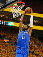 Thunder forward Paul George dunks during the first half Saturday.