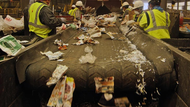 Workers pull out materials that should not have been put in a recycling bin and toss recyclables together by hand, at the Material Recovery Facility in Fontana, July 28, 2015.