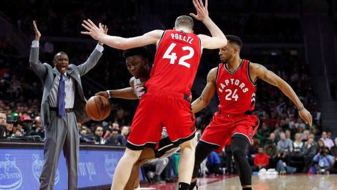 Pistons forward Stanley Johnson is defended by Raptors center Jakob Poeltl (42) and guard Norman Powell (24), as coach Dwane Casey reacts at the Palace of Auburn Hills on March 17, 2017.